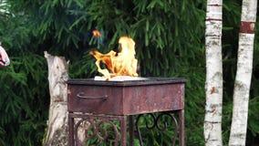 Το άτομο ανάβει την πυρκαγιά με την αντιστοιχία για να θερμάνει τους άνθρακες στη σχάρα φιλμ μικρού μήκους