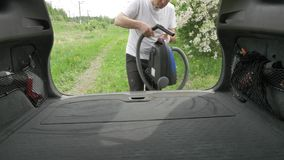 Το άτομο ανάβει hoover και αρχίζει hatchback τον κορμό με ηλεκτρική σκούπα απόθεμα βίντεο