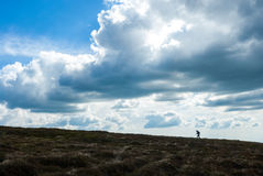 Το άτομο αναρριχείται επάνω στο λόφο Ορειβασία πεζοπορία Εντυπωσιακοί ουρανοί Στοκ Εικόνα