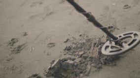 Το άτομο ανιχνεύει την άμμο στην παραλία από το ανιχνευτή μετάλλων και αρχίζει να σκάβει στην ακτή απόθεμα βίντεο