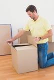 Το άτομο ανοίγει ένα κινούμενο κιβώτιο στο σπίτι Στοκ φωτογραφία με δικαίωμα ελεύθερης χρήσης