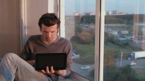 Το άτομο ανοίγει ένα netbook και αρχίζει να απασχολείται στη συνεδρίαση στο μπαλκόνι στο ηλιοβασίλεμα απόθεμα βίντεο