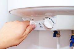 Το άτομο ανοίγει ανάβει το πίνακα ελέγχου λέβητα εγχώριων του ηλεκτρικού θερμοσιφώνων στοκ φωτογραφία