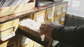 Το άτομο ανοίγει το συρτάρι βάσεων δεδομένων Ο νέος βιβλιοθηκάριος ανοίγει το δείκτη καρτών βιβλιοθηκών Αρχείο, βάση δεδομένων, έ απόθεμα βίντεο