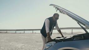 Το άτομο ανοίγει την κουκούλα του αυτοκινήτου του απόθεμα βίντεο