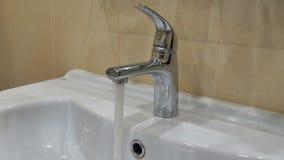 Το άτομο ανοίγει τη βρύση με το νερό απόθεμα βίντεο