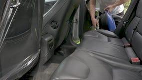 Το άτομο ανοίγει τη δευτερεύουσα πόρτα αυτοκινήτων που κρατά την ηλεκτρική σκούπα και τα κενά φιλμ μικρού μήκους