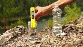 Το άτομο ανοίγει PH-meter συσκευών στο ποτήρι του νερού στην περιοχή βουνών Θέμα της υγείας και της οικολογίας Σε αργή κίνηση απόθεμα βίντεο