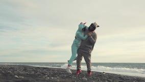 Το άτομο ανυψώνει τη φίλη του, και στο kigurumi και στέκεται στην παραλία κοντά στη θάλασσα φιλμ μικρού μήκους