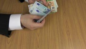 Το άτομο ανώτερων υπαλλήλων παίρνει και μετρά τα ευρο- τραπεζογραμμάτια 4K απόθεμα βίντεο