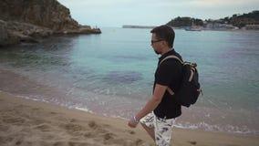 Το άτομο απολαμβάνει το μόνο περίπατο στην αμμώδη παραλία στο χρόνο λυκόφατος κοντά στο θαλάσσιο νερό απόθεμα βίντεο