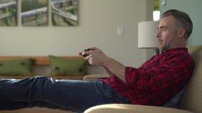 Το άτομο απολαμβάνει ένα τηλεοπτικό παιχνίδι μετά από την εργασία απόθεμα βίντεο