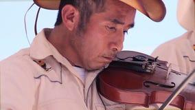 Το άτομο από την περιοχή παίζει ένα βιολί στο δημόσιο plaza κατά τη διάρκεια των του χωριού εορτασμών φιλμ μικρού μήκους
