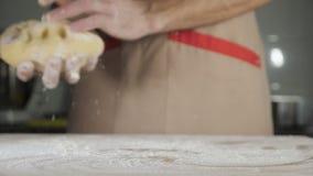 Το άτομο αρτοποιών αρχιμαγείρων στην ποδιά προετοιμάζει τη ζύμη φιλμ μικρού μήκους