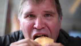 Το άτομο ατόμων τρώει τα σάντουιτς δαγκώνοντας hungrily μακριά ένα μεγάλο δάγκωμα, πίνοντας ένα ποτό απόθεμα βίντεο