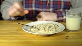 Το άτομο αυξάνει ένα κουτάλι και ωθεί αισθητά το κουάκερ πίσω στο πιάτο απόθεμα βίντεο