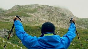 Το άτομο αυξάνει τα χέρια που στέκονται επάνω πίσω στο τοπ πρωί βουνών Κανένας αρσενικός αριθμός σκιαγραφιών προσώπου sportswear  φιλμ μικρού μήκους