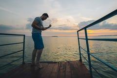 Το άτομο αυξάνεται χέρια επάνω στην αποβάθρα λιμνών Στοκ Φωτογραφία