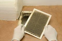 Το άτομο αφαιρεί τα κάγκελα εξαερισμού σκόνης Στοκ Εικόνες