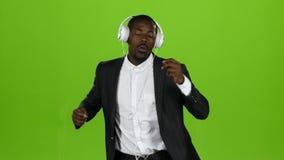 Το άτομο αφροαμερικάνων χορεύει λατινικά κινήσεων και ακούει τη μουσική στα ακουστικά πράσινη οθόνη απόθεμα βίντεο