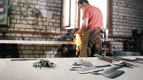 Το άτομο αλέθει τα εργαλεία σιδήρου μετάλλων με τα σπινθηρίσματα - σφυρηλατήστε το εργαστήριο απόθεμα βίντεο