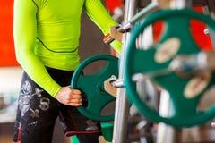 Το άτομο βάζει το βάρος στο φραγμό στη γυμναστική Στοκ Εικόνα