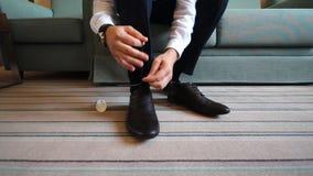 Το άτομο βάζει στα παπούτσια Εστίαση στις δαντέλλες απόθεμα βίντεο