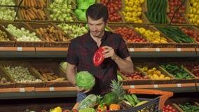 Το άτομο βάζει τα διαφορετικά λαχανικά στο κάρρο αγορών στοκ φωτογραφίες