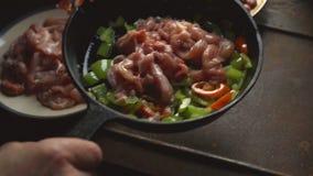 Το άτομο βάζει τα κομμάτια κοτόπουλου σε ένα τηγανίζοντας τηγάνι με το πιπέρι βίντεο απόθεμα βίντεο