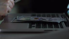 Το άτομο βάζει τα δολάρια σε ένα lap-top απόθεμα βίντεο