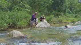 Το άτομο βάζει τα ψάρια στην τσάντα και το Φίσερ επιδιορθώνει το δίκτυο από τον ποταμό απόθεμα βίντεο