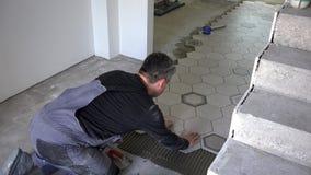 Το άτομο βάζει τα hexagon κεραμίδια στο πάτωμα Ανάδοχος που αγαπά την εργασία του απόθεμα βίντεο