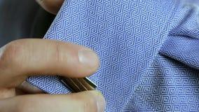 Το άτομο βγάζει το μανικετόκουμπο cloce επάνω φιλμ μικρού μήκους