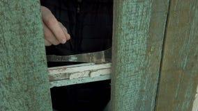 Το άτομο βγάζει τα τεμάχια του σπασμένου γυαλιού από το παράθυρο απόθεμα βίντεο