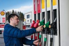 Το άτομο βενζινάδικων της Shell γεμίζει το αυτοκίνητο με τη βενζίνη στοκ εικόνα