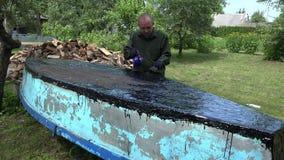 Το άτομο βιοτεχνών με τον καυστήρα αερίου και η πίσσα επισκευάζουν τη βάρκα του 4K φιλμ μικρού μήκους