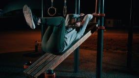 Το άτομο βρίσκεται στον υπαίθριο αθλητικό εξοπλισμό στο πάρκο και τα πόδια και την κοιλία κατάρτισης απόθεμα βίντεο