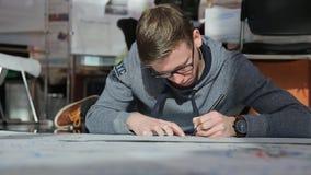 Το άτομο γκρίζο sportswear βρίσκεται στο πάτωμα και δημιουργεί το σχέδιο του σχεδίου της οικοδόμησης φιλμ μικρού μήκους
