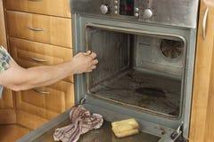 Το άτομο γονατίζει στο πάτωμα στην κουζίνα και καθαρίζει το φούρνο Στοκ Φωτογραφία