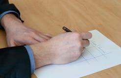 Το άτομο γράφει κάτι στη Λευκή Βίβλο. Εργασία γραφείων Στοκ Φωτογραφίες