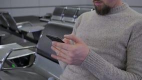 Το άτομο δακτυλογραφεί στην επίδειξη του κινητού τηλεφώνου φιλμ μικρού μήκους