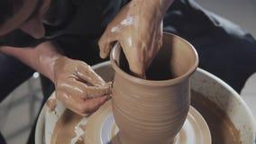 Το άτομο δημιουργεί το προϊόν στην περιστρεφόμενη αγγειοπλαστική τόρνου αγγειοπλαστών Τα χέρια δημιουργούν την κανάτα από τον άργ απόθεμα βίντεο