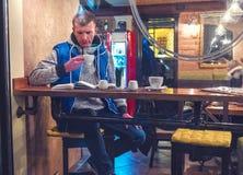 Το άτομο διάβασε το βιβλίο και πίνει τον καφέ στοκ εικόνα