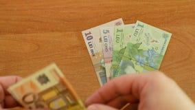 Το άτομο διέδωσε έξω το ρουμανικό lei στο γραφείο και έβαλε 50 ευρώ κατά μέρος απόθεμα βίντεο
