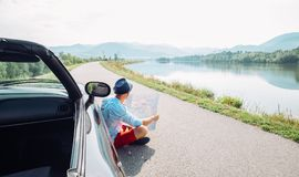 Το άτομο διαβάζει τη συνεδρίαση οδικών χαρτών κοντά στο καμπριολέ του στο γραφικό MO Στοκ Φωτογραφίες