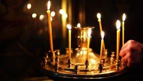 Το άτομο διορθώνει τα καίγοντας κεριά στο κηροπήγιο στη Ορθόδοξη Εκκλησία φιλμ μικρού μήκους