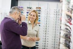 Το άτομο δοκιμάζει τα γυαλιά πλαισίων στοκ εικόνες με δικαίωμα ελεύθερης χρήσης