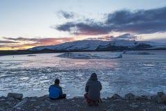 Το άτομο δύο φωτογράφων κάθεται από τη λιμνοθάλασσα παγετώνων jokulsarlon παίρνει phot στοκ φωτογραφία με δικαίωμα ελεύθερης χρήσης