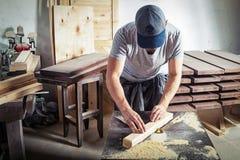 Το άτομο είναι ίσο με έναν ξύλινο φραγμό με μια μηχανή άλεσης Στοκ εικόνες με δικαίωμα ελεύθερης χρήσης