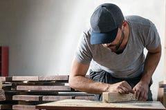 Το άτομο είναι ίσο με μια ξύλινη μηχανή άλεσης φραγμών Στοκ φωτογραφίες με δικαίωμα ελεύθερης χρήσης